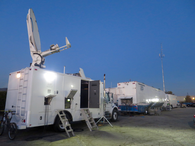 The NHRA truck compound features an F&F truck, a BSI truck, an Encompass Digital satellite uplink, and a Screenworks truck.